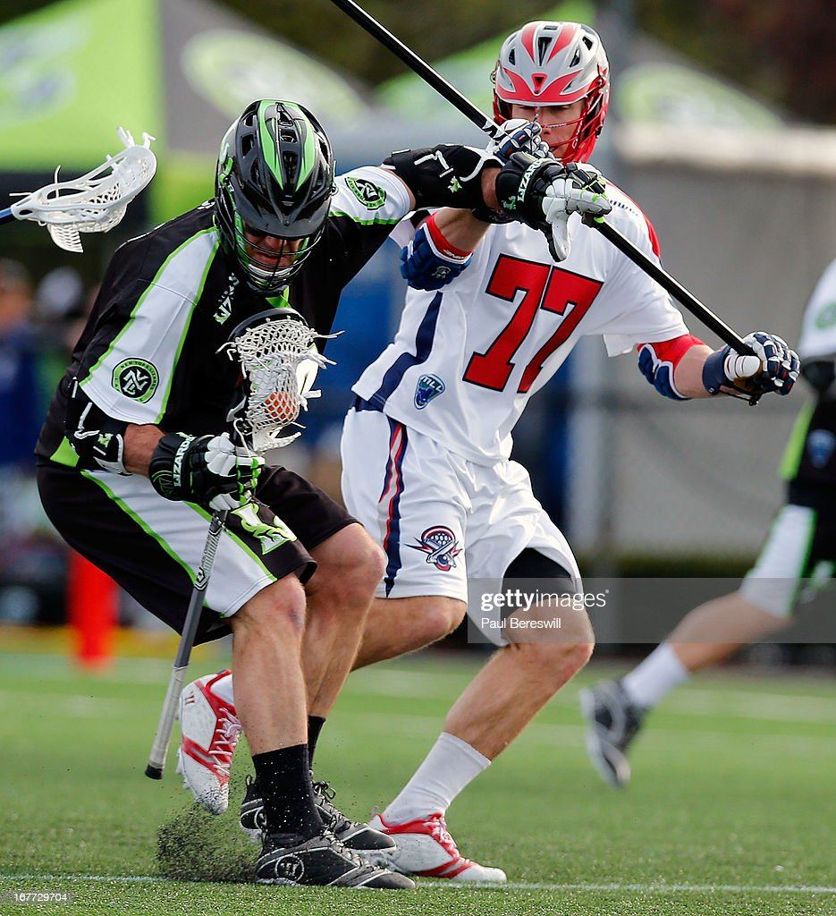 Stephen Peyser #18 of the New York Lizzards is checked by Kyle Sweeney #77 of the Boston Cannons in the second half of a Major League Lacrosse game at James M. Shuart Stadium on April 28, 2013 in Hempstead, New York.