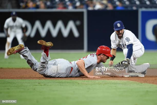 Stephen Piscotty of the St Louis Cardinals gets back to second base ahead of the tag of Carlos Asuaje of the San Diego Padres during the ninth inning...