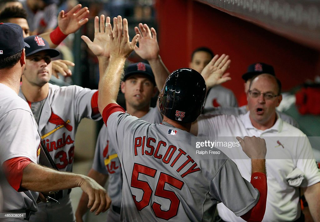 Stephen Piscotty #55 of the St Louis Cardinals is congratulated as he returns to the dugout after scoring against the Arizona Diamondbacks on an RBI double by teamate Kolten Wong #16 during the seventh inning of a MLB game at Chase Field on August 26, 2015 in Phoenix, Arizona. The cardinals defeated the Diamondbacks 3-1.