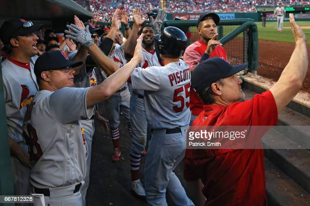 Stephen Piscotty of the St Louis Cardinals is greeted in the dugout by teammates after hitting a three run home run during the ninth inning against...