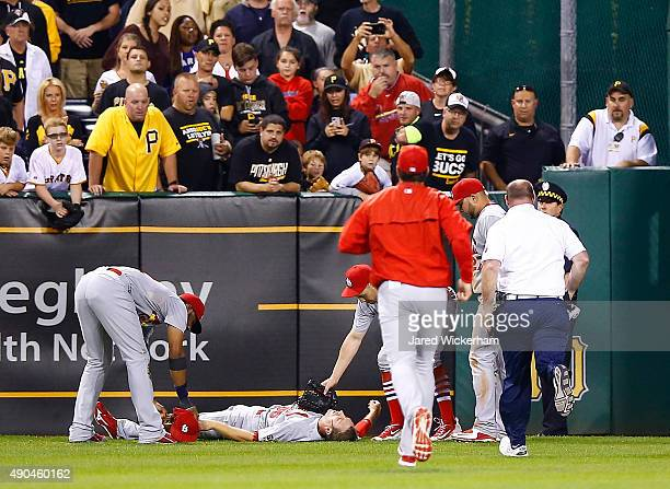 Stephen Piscotty of the St Louis Cardinals lays on the ground while teammates Peter Bourjos and Jason Heyward waits for the medical staff after...