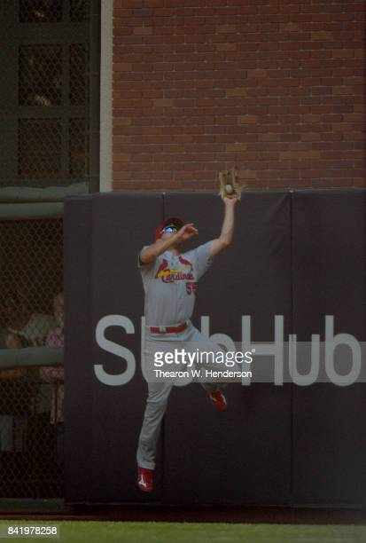 Stephen Piscotty of the St Louis Cardinals leaps at the wall to take a hit away from Nick Hundley of the San Francisco Giants in the bottom of the...