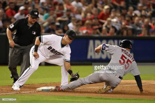 Stephen Piscotty of the St Louis Cardinals safely steals third base ahead of infielder Jake Lamb of the Arizona Diamondbacks during the sixth inning...