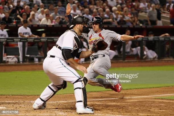 Stephen Piscotty of the St Louis Cardinals slides into home plate to score a run past catcher Chris Iannetta of the Arizona Diamondbacks during the...