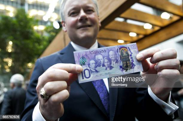 Stephen Poloz governor of the Bank of Canada stands for a photograph with a copy of a commemorative $10 note at Bank of Canada headquarters in Ottawa...