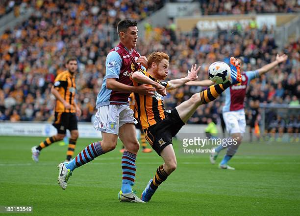 Stephen Quinn of Hull City competes for the ball with Ciaran Clark of Aston Villa during the Barclays Premier League match between Hull City and...