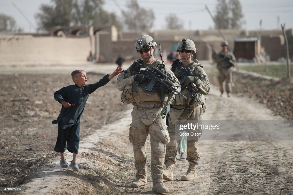Stephen Scroggs (L) from Oakland, California and SGT Shawn Williams with the U.S. Army's 4th squadron 2d Cavalry Regiment patrols through a village on March 3, 2014 near Kandahar, Afghanistan. President Obama recently ordered the Pentagon to begin contingency planning for a pullout from Afghanistan by the end of 2014 if Afghanistan President Hamid Karzai or his successor refuses to sign the Bilateral Security Agreement.