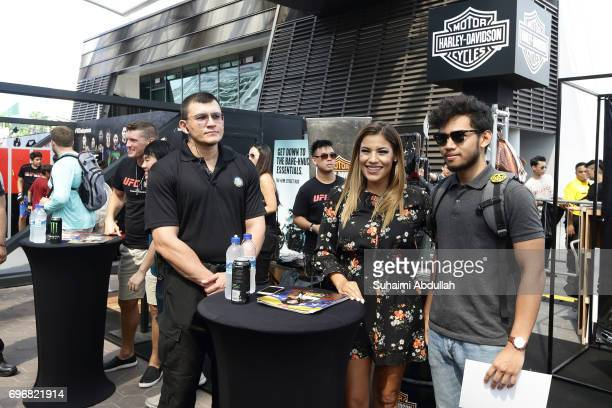 Stephen Thomson and Julianna Penna pose for a photo with fans at the Harley Davidson booth during the UFC Fan Experience at OCBC Square on June 17...