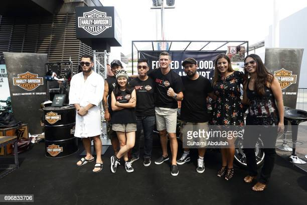Stephen Thomson Julianna Penna and Jorge Masdival pose for a photo at the Harley Davidson booth during the UFC Fan Experience at OCBC Square on June...