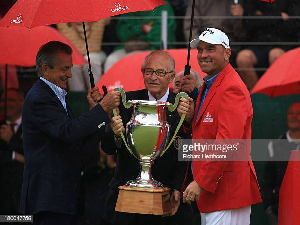Stephen Urquhart President of Omega and Gaston Barras President of the Organising Committee present Thomas Bjorn of Denmark with the trophy during...