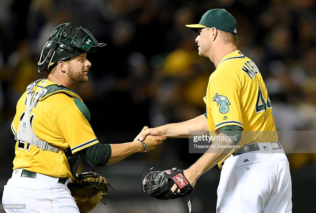 Stephen Vogt #21 and Ryan Madson #44 of the Oakland Athletics celebrates defeating the Seattle Mariners 5-3 at the Oakland Coliseum on August 12, 2016 in Oakland, California.