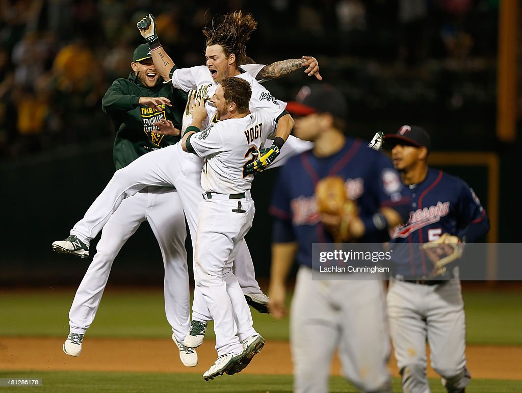 Stephen Vogt Brett Lawrie and Josh Reddick of the Oakland Athletics celebrate after a walk off win in the tenth inning against the Minnesota Twins at...