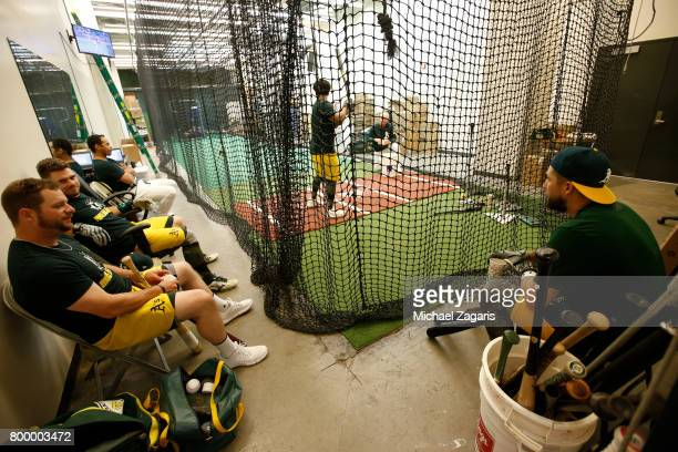 Stephen Vogt Josh Phegley and Trevor Plouffe of the Oakland Athletics sit at the indoor batting cage prior to the game against the Toronto Blue Jays...