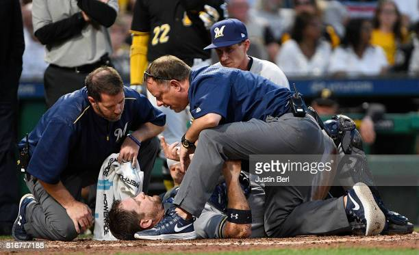 Stephen Vogt of the Milwaukee Brewers is checked out by trainers after a collision at home plate with Chad Kuhl of the Pittsburgh Pirates in the...