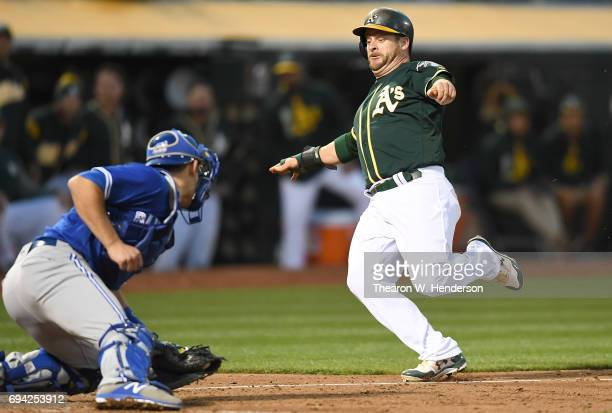 Stephen Vogt of the Oakland Athletics attempting to score from first base on a double by Mark Canha gets tagged out at home plate by Luke Maile of...