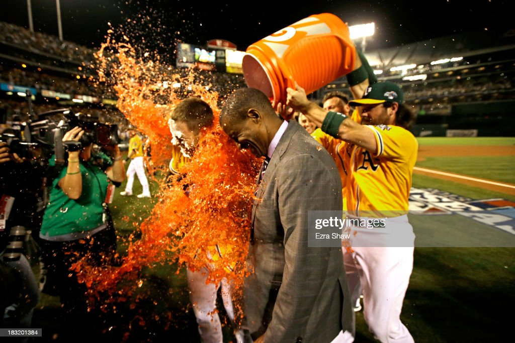 Stephen Vogt #21 of the Oakland Athletics gets dunked with a gatorade bath by teammate Josh Reddick #16 after scoring the game winning single against Al Alburquerque #62 of the Detroit Tigers in the ninth inning to win Game Two of the American League Division Series at O.co Coliseum on October 5, 2013 in Oakland, California.