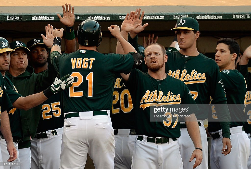 Stephen Vogt #21 of the Oakland Athletics is congratulated by teammates after he hit a sacrifice fly to score Jed Lowrie #8 in the second inning against the Cincinnati Reds at O.co Coliseum on June 25, 2013 in Oakland, California.