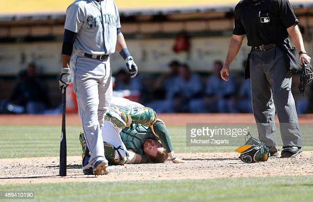 Stephen Vogt of the Oakland Athletics lays on the ground after getting hit in the groin during the game against the Seattle Mariners at Oco Coliseum...