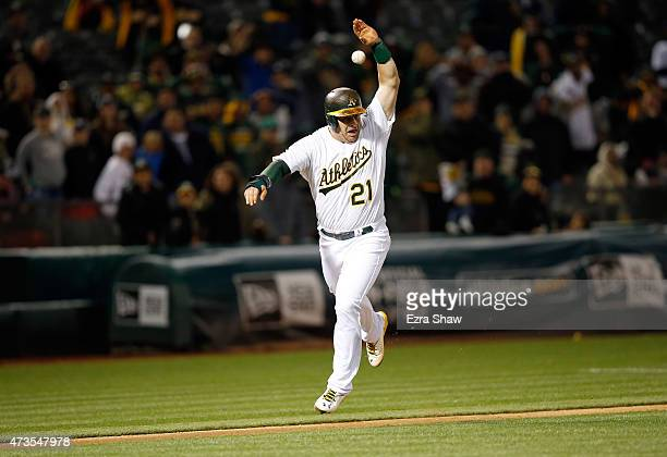 Stephen Vogt of the Oakland Athletics raises his arm as the ball goes over his head as he attempts to score the tying run in the ninth inning of...