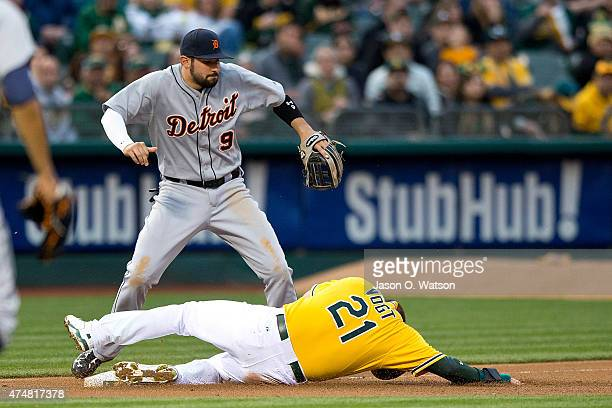 Stephen Vogt of the Oakland Athletics slides into third base after getting hit with a throw to Nick Castellanos of the Detroit Tigers during the...