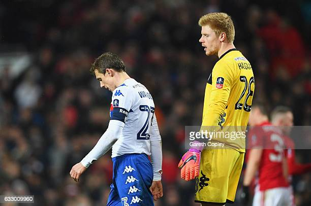 Stephen Warnock and Jakob Haugaard of Wigan Athletic look dejected as Chris Smalling of Manchester United scores their second goal during the...