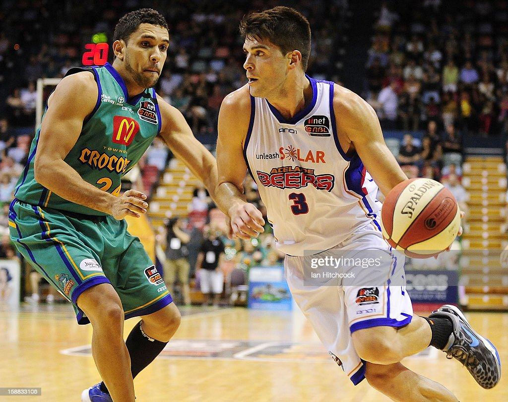 Stephen Weigh of the 36ers looks to drive past Michael Cedar of the Crocodiles during the round 12 NBL match between the Townsville Crocodiles and the Adelaide 36ers at Townsville Entertainment Centre on December 31, 2012 in Townsville, Australia.