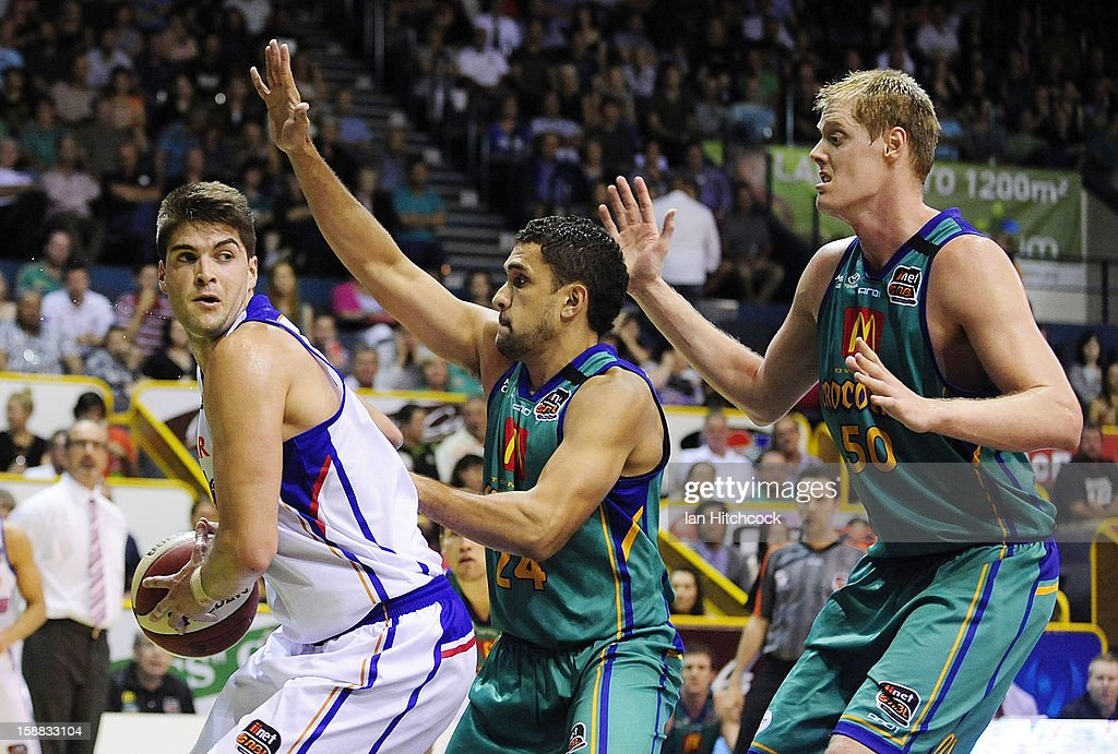Stephen Weigh of the 36ers looks to get the ball away despite the defence of Michael Cedar and <a gi-track='captionPersonalityLinkClicked' href=/galleries/search?phrase=Luke+Nevill&family=editorial&specificpeople=835195 ng-click='$event.stopPropagation()'>Luke Nevill</a> of the Crocodiles during the round 12 NBL match between the Townsville Crocodiles and the Adelaide 36ers at Townsville Entertainment Centre on December 31, 2012 in Townsville, Australia.