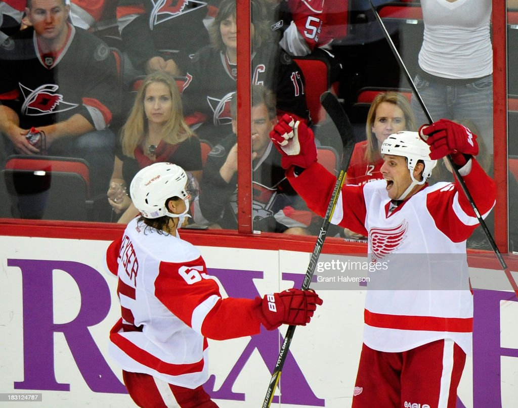 Stephen Weiss #90 and Danny DeKeyser #65 of the Detroit Red Wings celebrate after Weiss's game-winning goal in overtime against the Carolina Hurricanes during play at PNC Arena on October 4, 2013 in Raleigh, North Carolina. The Red Wings defeated the Hurricanes 3-2 in overtime.