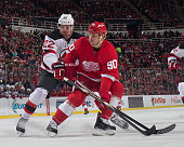 Stephen Weiss of the Detroit Red Wings battles for the puck with Eric Gelinas of the New Jersey Devils during the annual New Year's eve game on...