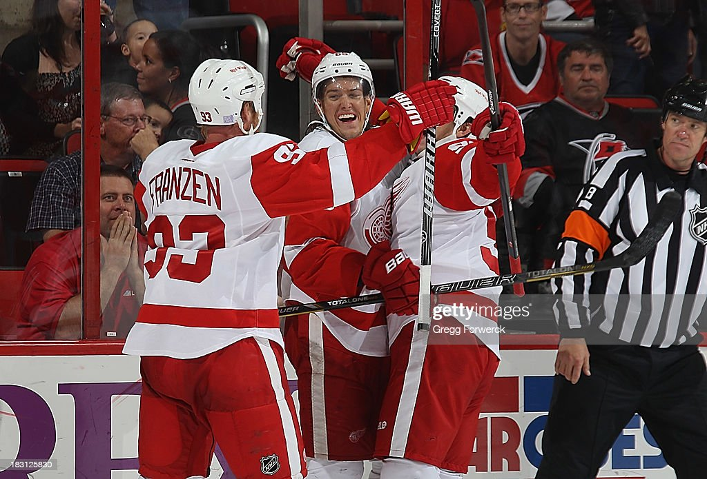 Stephen Weiss #90 of the Detroit Red Wings celebrates his game-winning goal in overtime with teammates <a gi-track='captionPersonalityLinkClicked' href=/galleries/search?phrase=Johan+Franzen&family=editorial&specificpeople=624356 ng-click='$event.stopPropagation()'>Johan Franzen</a> #93 and Danny DeKeyser #65 during an NHL game against the Carolina Hurricanes on October 4, 2013 in the home opener at PNC Arena in Raleigh, North Carolina.