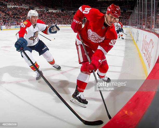 Stephen Weiss of the Detroit Red Wings handles the puck in the corner as Jussi Jokinen of the Florida Panthers pressures him during a NHL game on...