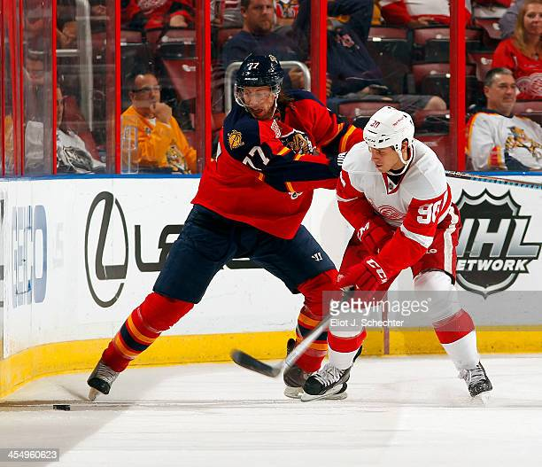 Stephen Weiss of the Detroit Red Wings tangles with Tom Gilbert of the Florida Panthers at the BBT Center on December 10 2013 in Sunrise Florida
