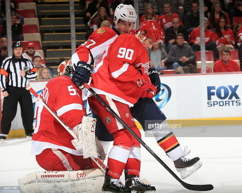 Stephen Weiss #90 of the Detroit Red Wings ties up <a gi-track='captionPersonalityLinkClicked' href=/galleries/search?phrase=Marcel+Goc&family=editorial&specificpeople=541626 ng-click='$event.stopPropagation()'>Marcel Goc</a> #57 of the Florida Panthers in front of teammate <a gi-track='captionPersonalityLinkClicked' href=/galleries/search?phrase=Jonas+Gustavsson&family=editorial&specificpeople=886789 ng-click='$event.stopPropagation()'>Jonas Gustavsson</a> #50 during an NHL game at Joe Louis Arena on December 7, 2013 in Detroit, Michigan.