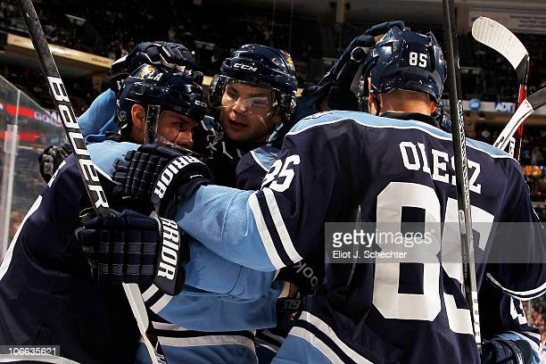 Stephen Weiss of the Florida Panthers celebrates his goal while hugging teammates Michael Frolik and Rostislav Olesz against the Carolina Hurricanes...