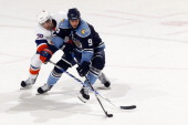 Stephen Weiss of the Florida Panthers crosses sticks with Jack Hillen of the New York Islanders at the BankAtlantic Center on March 19 2011 in...