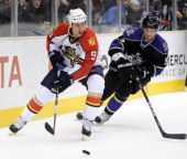 Stephen Weiss of the Florida Panthers looks to pass as he is chased by Peter Harrold of the Los Angeles Kings at the Staples Center on December 2...