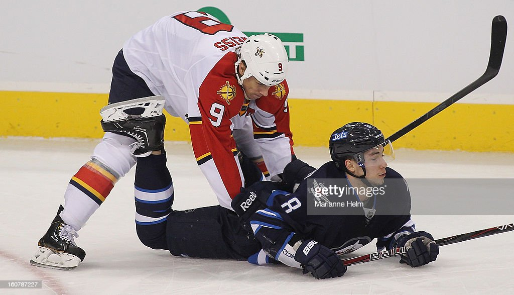 Stephen Weiss #9 of the Florida Panthers pushes Alexander Burmistrov #8 of the Winnipeg Jets into the ice during NHL action on February 5, 2013 at the MTS Centre in Winnipeg, Manitoba, Canada.