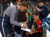 Stephen Weiss of the Florida Panthers signs an autograph for a young fan after the game against the Washington Capitals on April 9 2011 at the...