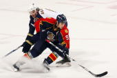 Stephen Weiss of the Florida Panthers skates with the puck against Ron Hainsey of the Atlanta Thrashers at the BankAtlantic Center on December 16...