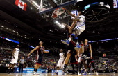 J Stephens of the Memphis Tigers dunks on Matthew Dellavedova of the St Mary's Gaels in the second half during the second round of the 2013 NCAA...