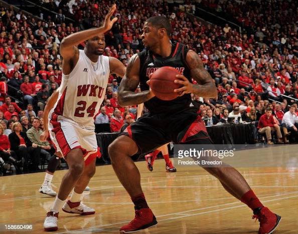 Stephon Drane of the Western Kentucky Hilltoppers defends Chane Behanan of the Louisville Cardinals at Bridgestone Arena on December 22 2012 in...