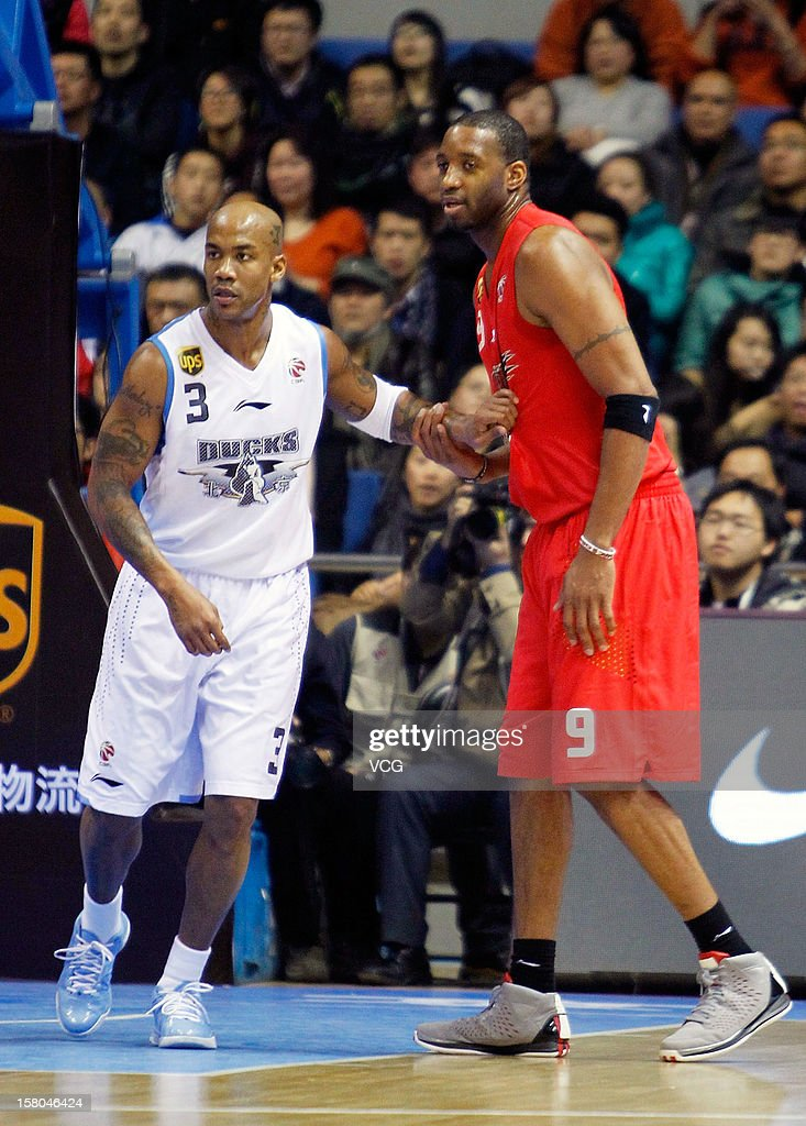 <a gi-track='captionPersonalityLinkClicked' href=/galleries/search?phrase=Stephon+Marbury&family=editorial&specificpeople=201496 ng-click='$event.stopPropagation()'>Stephon Marbury</a> #3 of Beijing Ducks defends against <a gi-track='captionPersonalityLinkClicked' href=/galleries/search?phrase=Tracy+McGrady&family=editorial&specificpeople=201486 ng-click='$event.stopPropagation()'>Tracy McGrady</a> #9 of Qingdao Eagles during the seventh round of the CBA 12/13 game at Shougang Basketball Centre on December 9, 2012 in Beijing, China.