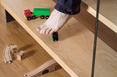 Close-up of young man's foot on stairs stepping on boy's toy