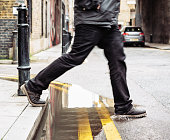 A man stepping over a puddle between the pavement and street.