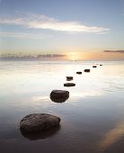 Stepping stones over water at sunrise