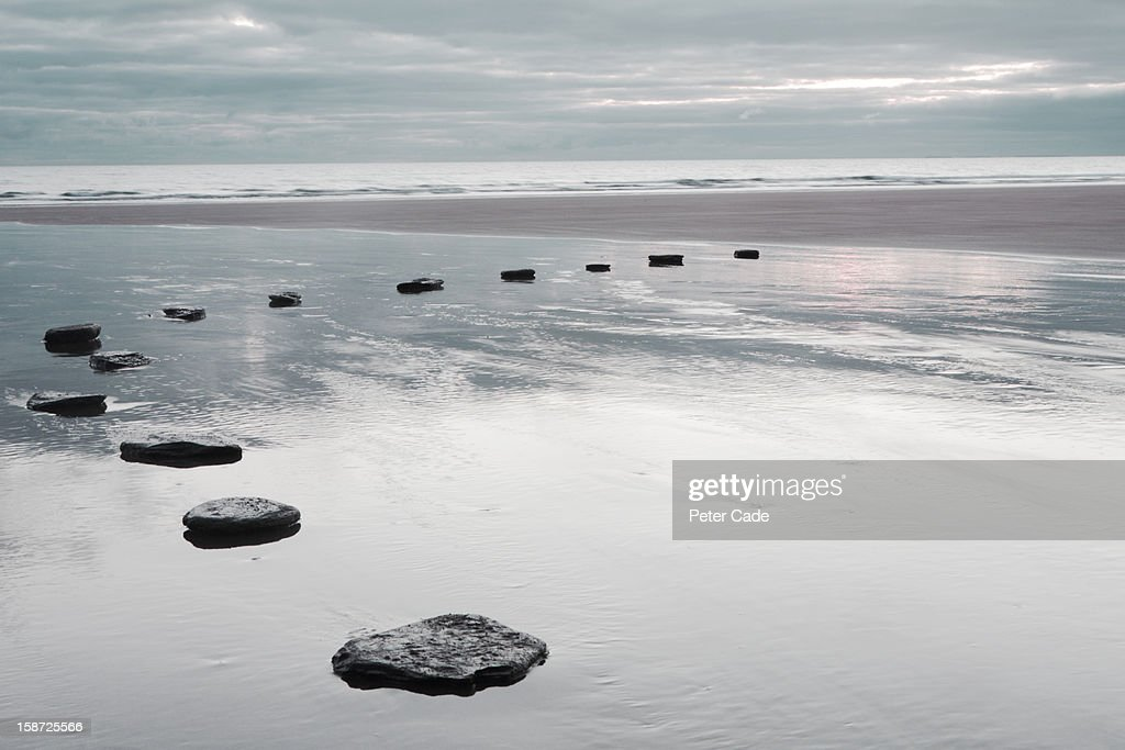stepping stones over water on beach : Stock Photo