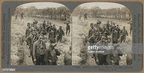 A stereo card image of American troops preparing to enter a gasfilled trench during a gas mask drill at Fort Dix New Jersey USA circa 1917