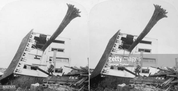 Stereoscopic image of a house fallen on its side with the trunk of an uprooted tree protruding from one window Johnstown Pennsylvania A man poses on...