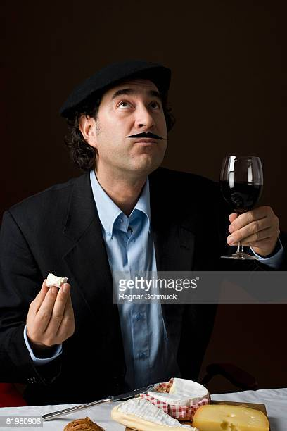 Stereotypical French man with French cheese and a glass of red wine