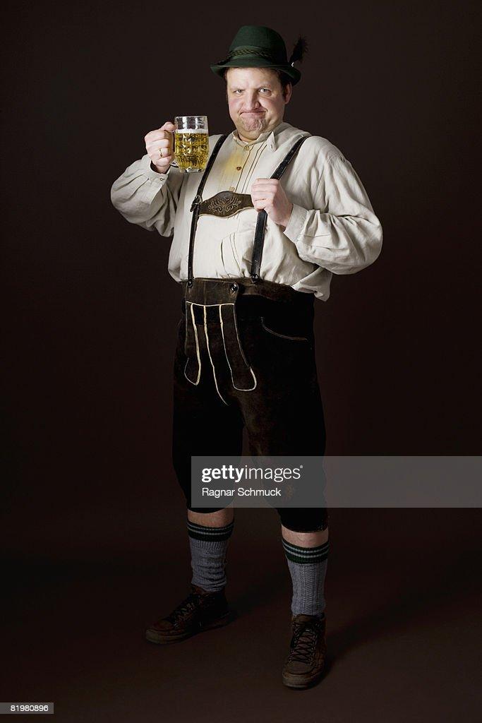 Stereotypical German man in Bavarian costume raising a beer in toast